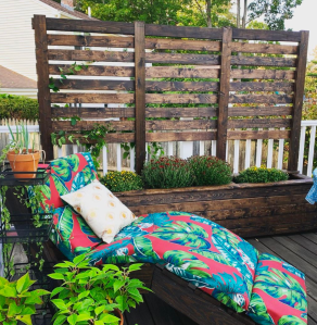 A dark wood planter with a six foot tall trellis on the back. In front of it is a wooden chaise lounge with a brightly colored cushion.