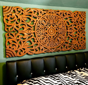 A long rectangle carved in an intricate floral design, hanging on the wall over a bed.